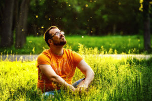 40827717 - a happy thoughtful dreamer man is sitting on green grass in a park at sunny summer day and looking into future. concept of relaxation, wellbeing, lifestyle.